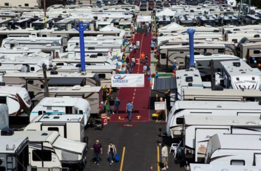 Photo of Chesaco RV dealership. There are dozens of RVs lined up on either side of a red carpet lined with ballons where people are walking and looking at the RVs.