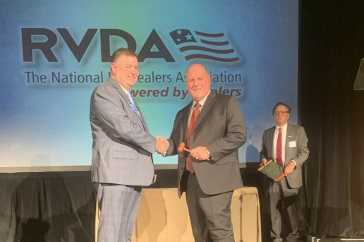 Outgoing RVDA Chairman Mike Regan passes the gavel to new Chairman Ron Shepherd, while RVDA President approaches to award a plaque to Regan.