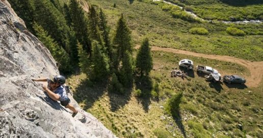 Photo of man climbing rocks with two pickup trucks and travel trailers below.