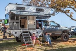 Photo of two people lounging in front of a truck camper at Overland Expo East 2019.