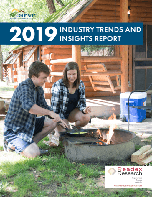 The front cover for the 2019 ARVC Industry Trends & Insights Report shows a picture of a man and a woman kneeling in the grass beside a campfire in front of a cabin. The man is cooking eggs in a frying pan over the fire while the woman watches.