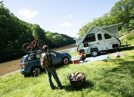 A photograph of a man standing next to a fire pit and a woman on a picnic blanket. Their SUV and pop-up travel trailer are parked behind them on a grassy river bank.Aliner camper lifestyle photo