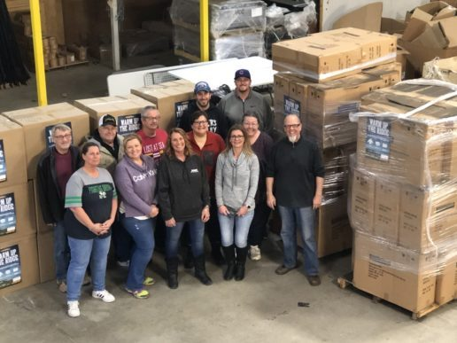 A phtograph of about a dozen people standing in front of pallets loaded high with boxes in a warehouse setting. Brent Stevens, general manager of Forest River's XLR division (right) and members of his service group begin putting pallets of donated items together.
