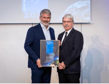 A photo of two men holding the LCI European Innovation award