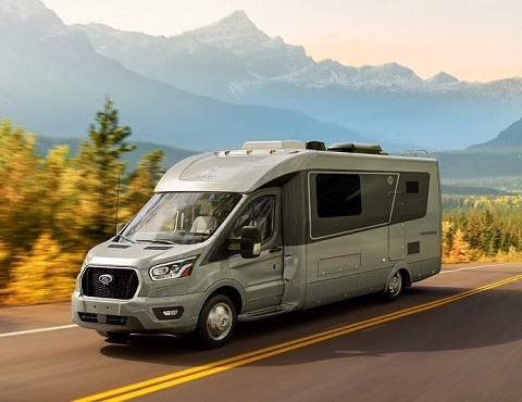 A picture of a gray Type C RV on a two-lane highway with mountains and trees in the background.