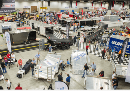A photo taken from above of people setting up a trailer show in a giant expo hall