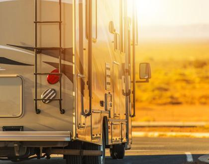 A picture of an RV driving down the road away from the camera with the setting sun glaring off the side of the RV