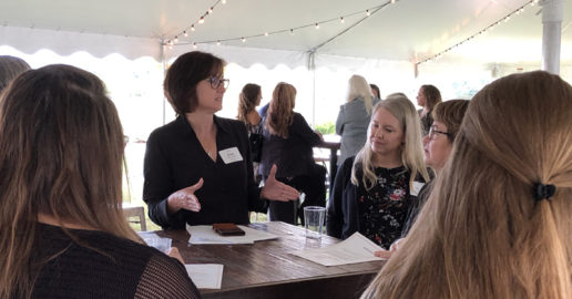 RV Women's Alliance president Susan Carpenter speaks to other women at a table inside of a white tent