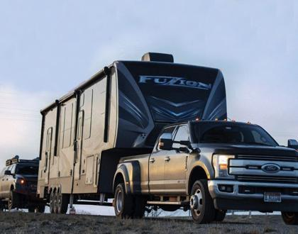A picture of a Ford pickup truck towing a Fuzion fifth wheel. An SUV follows.