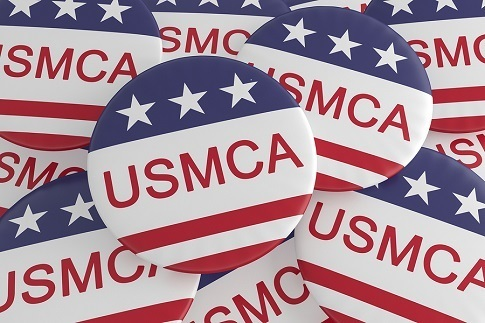 """A picture of a pile of campaign buttons that say, """"USMCA"""" on them. The buttons have a strip of blue with white stars on top and red and white stripes on the bottom."""