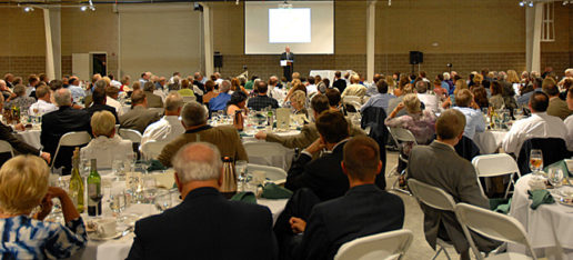 A photograph from the audience's perspective of a man standing at a podium addressing a conference hall full of people. This is the Recreational Vehicle and Motorhome Hall of Fame Induction Dinner