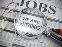 """A picture of a newspaper with the word """"Jobs"""" at the top of the page. A pair of reading glasses, a magnifying glass and a red marker all sit on top of the newspaper. The words """"We Are Hiring"""" are visible under the magnifying glass."""