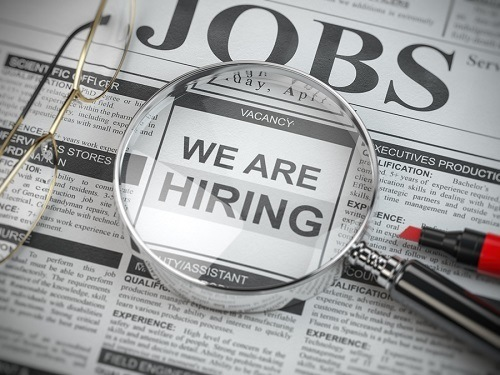 "A picture of a newspaper with the word ""Jobs"" at the top of the page. A pair of reading glasses, a magnifying glass and a red marker all sit on top of the newspaper. The words ""We Are Hiring"" are visible under the magnifying glass."