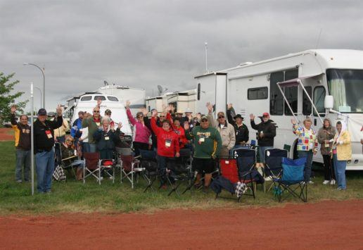 A photograph of about 24 people standing and sitting in lawn chairs in front of their RVs on a cloudy day.