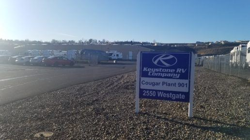 """Photo of the exterior of the Keystone RV Plant in Oregon. A sign that reads """"Keystone RV Company, Cougar Plant 901, 2550 Westgate"""" stands in a rock bed beside a parking lot full of cars and RVs. There is a warehouse at the far end of the parking lot."""