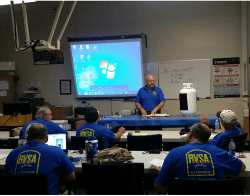 A picture of a man standing in front of a classroom of 5 students. The students are seated facing away from the camera and are all wearing blue RVSA t-shirts. The instructor is standing at a table with a propane tank on it. There is a projection screen and a white board on the wall behind him.