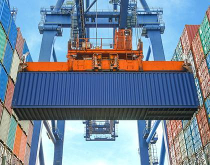 A picture of a crane moving a blue shipping container, with walls of multi-colored shipping containers stacked on either side