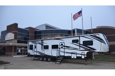A picture of a Jacyco fifth wheel toy hauler in front of a building and an American flag