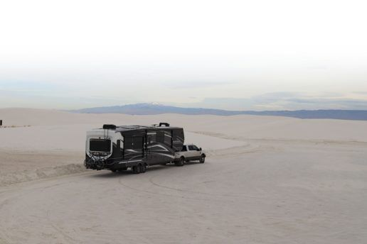 A truck pulls a Keystone RV 2020 Montana Super SolarFlex through a white, sandy desert with mountains in the distant background