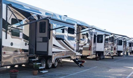 A row of clean, shiny travel trailers on a parking lot with their awnings out and doors open.