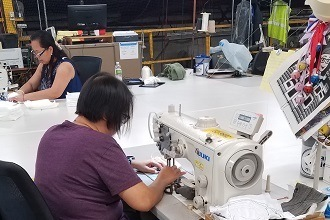 A photograph of two women who work for Winnebago's Stitchcraft sewing medical masks