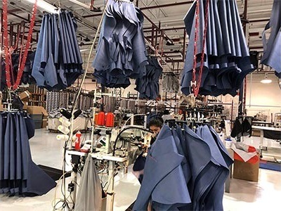 A photograph of personal protective equipment hanging up in a Covercraft manufacturing warehouse.