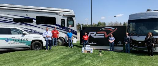A photo of seven REV Group associates standing on grass in front of two RVs and an Adams County Emergency Medical Service truck with medicals masks they are donating to the Adams Memorial hospital.