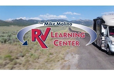"A picture of a Type C RV driving down a highway with prairie brush on the side of the road and mountains in the background. A graphic saying, ""The Mike Molino RV Learning Center"" has been superimposed on the image."