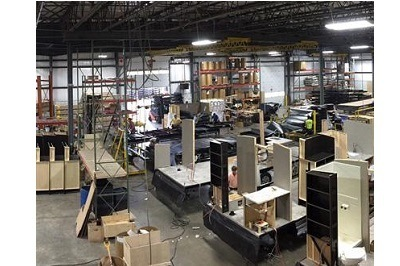 A picture of the inside of a manufacturing plant. There are shelves and boxes and scraps of wood around various work stations.
