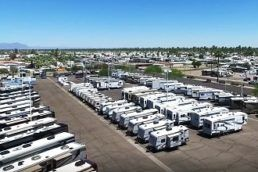 An aerial photograph of an RV dealership lot with dozens of RVs lined up neatly