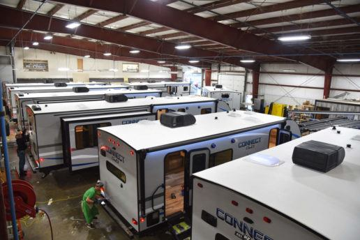 A photograph of about six KZ RV travel trailers lined up side-by-side in a manufacturing warehouse. There are a couple of employees working on the backs of different RVs.