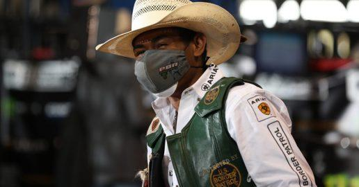 A photo of a professional bull rider wearing a protective face mask