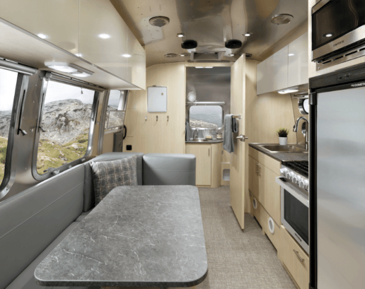 An image of the new 2021 Flying Cloud Airstream interior. The photo shows through the kitchen into the bathroom at the rear of the trailer. The kitchen has a gray dinette under some white cabinetry on the left and a sink, range and refrigerator on the right.