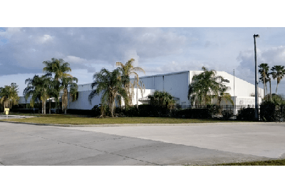 a photograph of a warehouse surrounded by palm trees