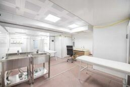 A photograph of the interior of a mobile medical unit, showing two sinks, an exam table, a desk and an office chair