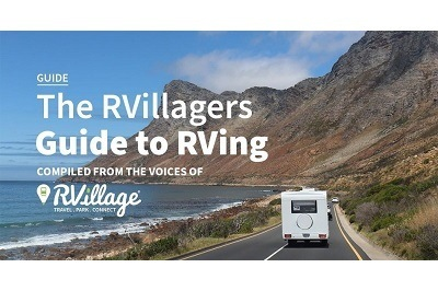 "A picture of the back of an RV driving away from the camera down an oceanside highway. Text imposed on the image says, ""Guide. The RVillagers Guide to RVing. Compiled from the voices of RVillage."""