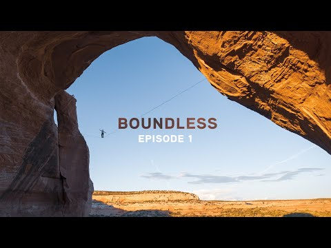 A screenshot of the Boundless' first episode. The image shows a man on a tightrope stretched across a giant red rock arch in the middle of a desert landscape under a clear blue sky.