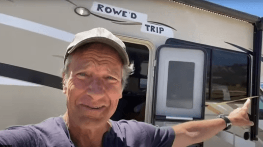 A picture of Mike Rowe standing in front of an RV