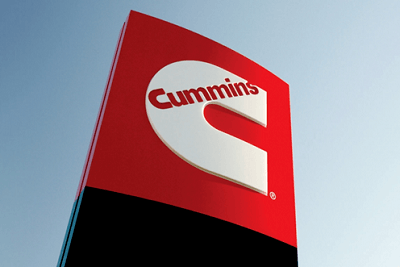 A picture of a sign with the Cummins logo in front of a clear blue sky