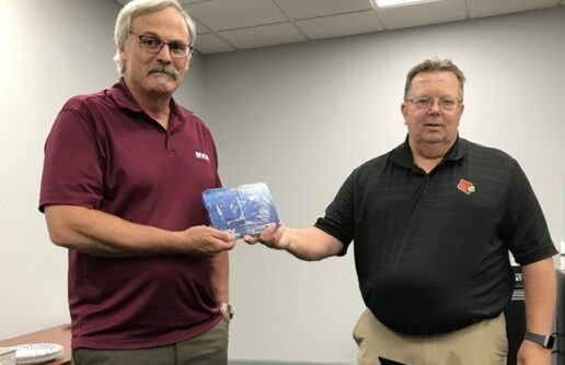 Picture of Greg Wishmeyer receiving an award for 20 years of Service with RVIA from RVIA Chief Inspector Curt Richardson.