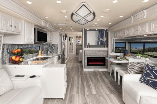 A picture of the inside of Holiday Rambler Armada 44LE. The decorating features white sofas and cabinetry with gray flooring and walls. The picture shows from the living room through the RV's kitchen back towards the bedroom.