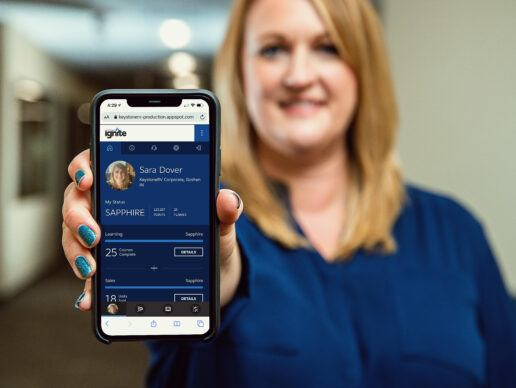 A picture of a woman holding a smart phone showing off the new Keystone Ignite Sales App