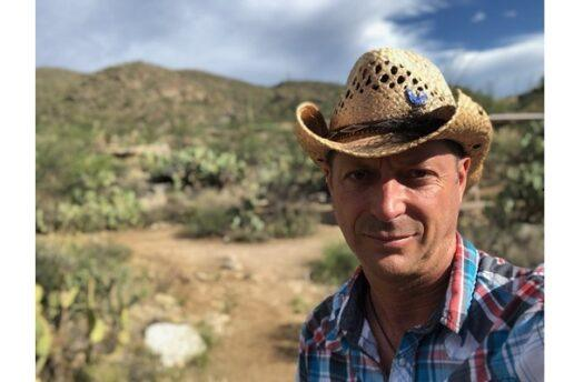 A photograph of Scott Watson of Go Small Live Large. Watson is wearing a straw cowboy hat and a plaid shirt. The desert opens up behind him. One big cloud is overtaking the sky.