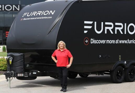 """A photo of TracTracy Anglemeyer, Vice President of Sale, Specialty Vehicles. Angelmeyer is standing in front of a travel trailer that says, """"Furrion. Discover more at www.furrion.com"""" on the side."""