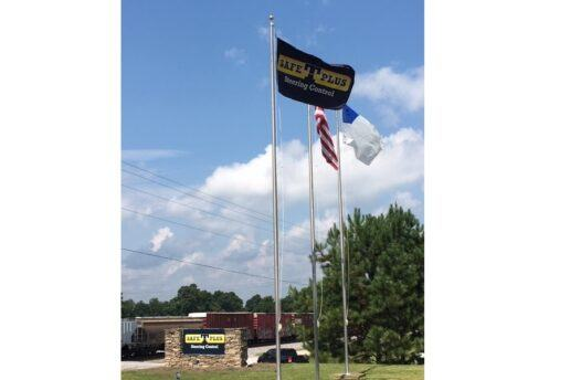 """A picture of three flags flapping in the wind in front of a a cloudy sky. One of the flags says """"Safe T Plus Steering Control"""" on it."""