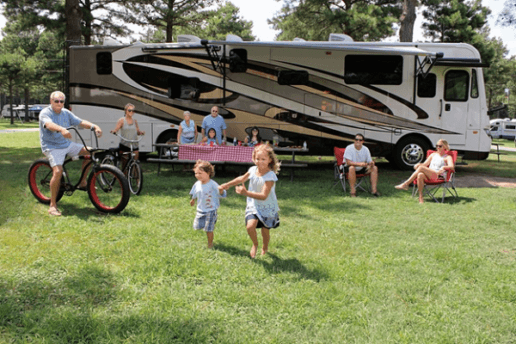 A photo of a family spending time together in the grass outside of a type A motorhome. A couple of adults are sitting on bikes. Two children are running on the grass. Four people are sitting at a picnic table, and two more people are lounging in camping chairs off to the side.