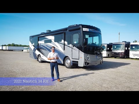 A screenshot of the video showing off Holiday Rambler's 2021 Nautica 34RX. The screenshot shows a man standing in front of a type A motorhome in the middle of a gravel parking lot.