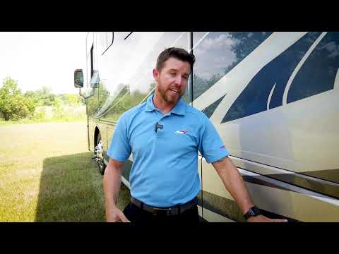 A picture of a man standing beside a type A motorhome