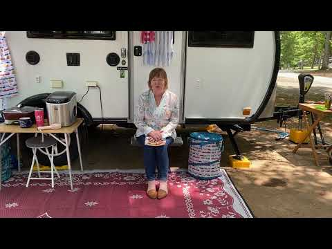 The landing image for a video. The picture shows a woman sitting on an RV step where she has set up camp. There is a maroon rug on the ground, and there are several tables arranged around the RV.