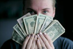 A photograph of a woman holding bills in varying monetary denominations fanned out in front of her face.